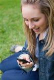 Muchacha rubia atractiva que muestra su sorpresa mientras que recibe un te Imágenes de archivo libres de regalías