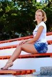 Muchacha rubia atractiva que presenta en una falda corta de los pantalones vaqueros Imagen de archivo libre de regalías