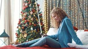 Muchacha rubia atractiva que se sienta en un sofá en casa y que manda un SMS en su teléfono almacen de metraje de vídeo