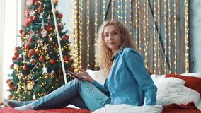 Muchacha rubia atractiva que se sienta en un sofá en casa y que manda un SMS en su teléfono metrajes