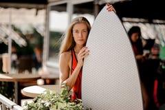 Muchacha rubia atractiva que sostiene un wakeboard blanco y que lo mira foto de archivo libre de regalías