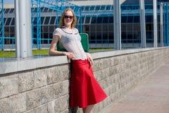 Muchacha rubia atractiva sonriente que desgasta la falda roja imágenes de archivo libres de regalías