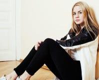 Muchacha rubia bastante adolescente de los jóvenes que se sienta en la desesperación del piso en casa Fotos de archivo