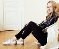 Muchacha rubia bastante adolescente de los jóvenes que se sienta en la desesperación del piso en casa Foto de archivo