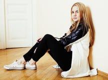 Muchacha rubia bastante adolescente de los jóvenes que se sienta en la desesperación del piso en casa Fotografía de archivo libre de regalías