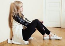 Muchacha rubia bastante adolescente de los jóvenes que se sienta en solo triste de la desesperación del piso en casa, concepto de Fotografía de archivo
