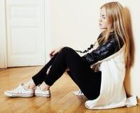 Muchacha rubia bastante adolescente de los jóvenes que se sienta en solo triste de la desesperación del piso en casa, concepto de Imágenes de archivo libres de regalías