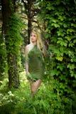 Muchacha rubia bastante joven con el pelo largo en vestido verde como un duende que se coloca en el bosque verde en donde los árb imagen de archivo
