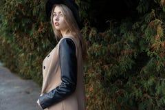 Muchacha rubia bastante linda triste sola con los ojos azules y los labios llenos en sombrero negro y capa que camina en bosque d Foto de archivo libre de regalías