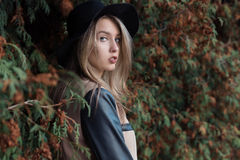 Muchacha rubia bastante linda triste sola con los ojos azules y los labios llenos en sombrero negro y capa que camina en bosque d fotografía de archivo libre de regalías