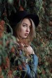 Muchacha rubia bastante linda triste sola con los ojos azules y los labios llenos en sombrero negro y capa que camina en bosque d Fotos de archivo