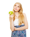 Muchacha rubia bastante pensativa con la manzana verde Fotografía de archivo
