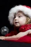 Muchacha rubia bastante pequeña con ropa y el sombrero rojos Foto de archivo