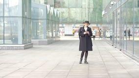 Muchacha rubia bonita en textos negros del sombrero de la capa en el teléfono que camina a lo largo de la pared constructiva de l almacen de video