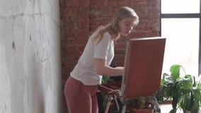 Muchacha rubia bonita joven con la situaci?n del cepillo y de la paleta cerca de la imagen del dibujo del caballete Arte, creativ almacen de metraje de vídeo