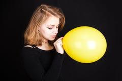 Muchacha rubia caucásica con el globo amarillo en negro Fotografía de archivo libre de regalías