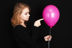 Muchacha rubia caucásica que señala con el globo del rosa del finger Imagenes de archivo