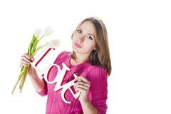 Muchacha rubia con amor decorativo de la palabra y tulipanes blancos fotografía de archivo libre de regalías