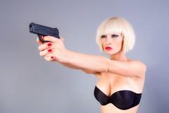 Muchacha rubia con el arma Foto de archivo