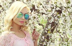 Muchacha rubia con el aviador Sunglasses sobre Cherry Blossom. Primavera imagen de archivo libre de regalías