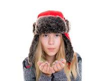 Muchacha rubia con el casquillo y la bufanda de la piel que soplan adentro a la cámara Fotografía de archivo libre de regalías