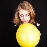 Muchacha rubia con el globo amarillo en negro Fotos de archivo