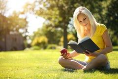 Muchacha rubia con el libro y Apple en hierba verde Fotos de archivo libres de regalías