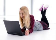 Muchacha rubia con el ordenador portátil que miente en el piso Fotos de archivo