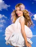Muchacha rubia con el pelo que sopla del vestido de la moda en cielo azul Foto de archivo libre de regalías