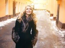 Muchacha rubia con el pelo rizado largo en abrigo de pieles Fotos de archivo
