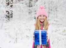 Muchacha rubia con el regalo en bosque del invierno Imágenes de archivo libres de regalías
