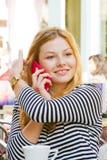 Muchacha rubia con el teléfono elegante Foto de archivo libre de regalías