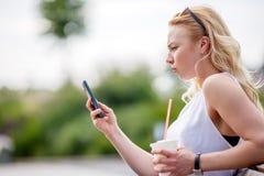 Muchacha rubia con el teléfono móvil que se sienta en banco Imágenes de archivo libres de regalías
