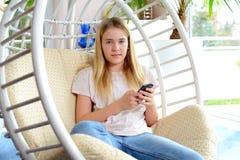 Muchacha rubia con el teléfono que se sienta en silla Imagenes de archivo