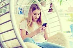 Muchacha rubia con el teléfono que se sienta en silla Imagen de archivo libre de regalías