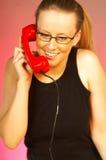Muchacha rubia con el teléfono rojo Imagen de archivo libre de regalías