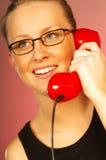 Muchacha rubia con el teléfono rojo Fotografía de archivo
