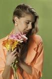 Muchacha rubia con en la naranja que sostiene las flores, fotos de archivo