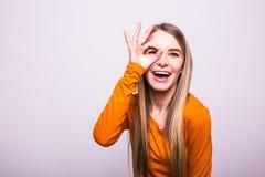 Muchacha rubia con gesto aceptable en blanco Foto de archivo