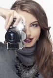 Muchacha rubia con la cámara que mira adelante Muchacha rubia hermosa con la cámara retra negra en estudio contra la pared blanca Imagenes de archivo