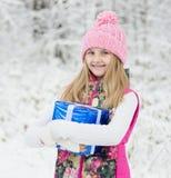 Muchacha rubia con la caja de regalo azul en bosque del invierno Imágenes de archivo libres de regalías