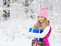 Muchacha rubia con la caja de regalo azul en bosque del invierno Fotos de archivo libres de regalías