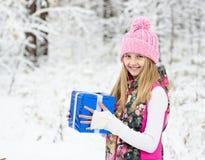 Muchacha rubia con la caja de regalo azul en bosque del invierno Foto de archivo libre de regalías