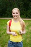 Muchacha rubia con la mochila roja en el parque en el verano Fotografía de archivo libre de regalías