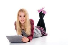 Muchacha rubia con la PC de la tableta que miente en el piso Imágenes de archivo libres de regalías