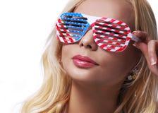Muchacha rubia con las gafas de sol de las banderas americanas. Imágenes de archivo libres de regalías