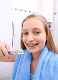 Muchacha rubia con los apoyos que sonríe mientras que cepilla sus dientes Fotografía de archivo