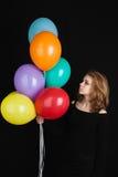 Muchacha rubia con los globos coloridos sobre negro Fotografía de archivo libre de regalías