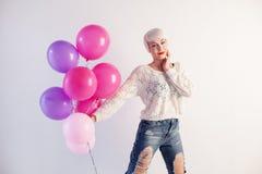 Muchacha rubia con los globos y el regalo en un día de fiesta Foto de archivo libre de regalías