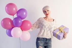 Muchacha rubia con los globos y el regalo en un día de fiesta Imagen de archivo libre de regalías